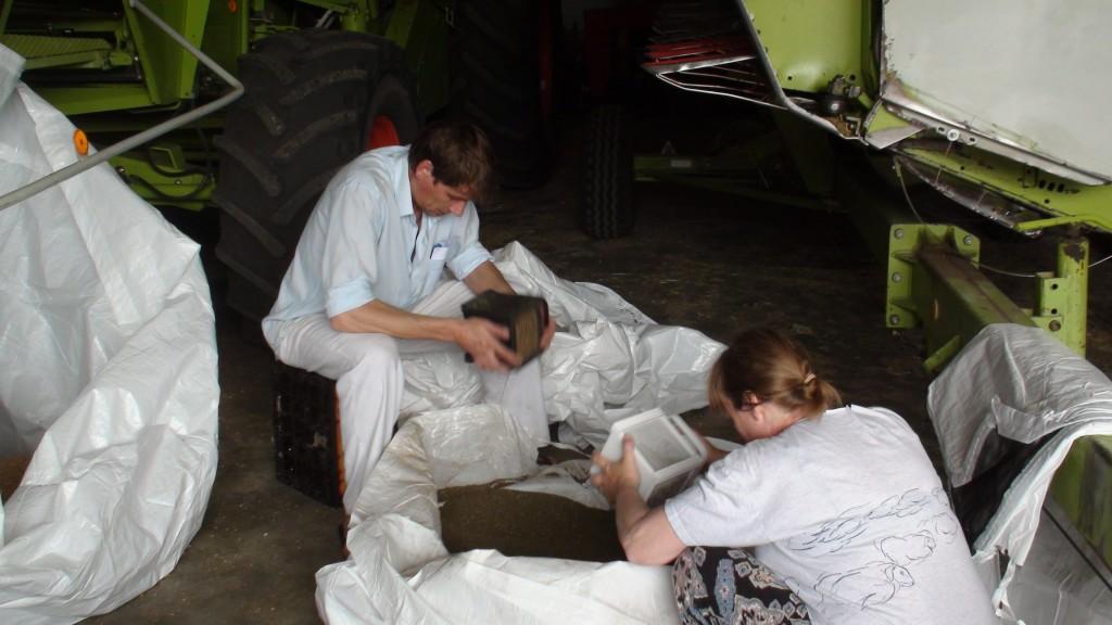Arie Koster en Selma Kromhout zeven het graan met het tuinlampje; gezien de mogelijkheden werkt dat voor vandaag even goed